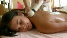 Soaked dark-haired lying on massage bed getting her body stimulated on hard